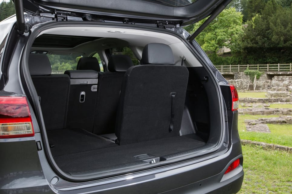 Large third row cupholder stations over the wheel arches and the seat belts can be cumbersome if you are carrying larger items.