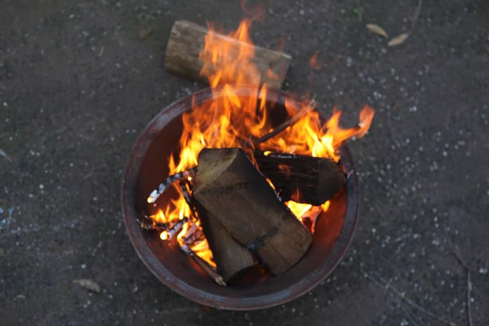Give it time to establish a sustained flame before adding three short logs over the top of the fire.
